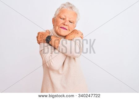 Senior grey-haired woman wearing turtleneck sweater standing over isolated white background Hugging oneself happy and positive, smiling confident. Self love and self care