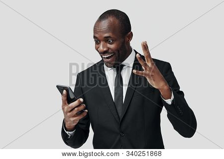 Surprised Young African Man In Formalwear Using Smart Phone And Smiling While Standing Against Grey
