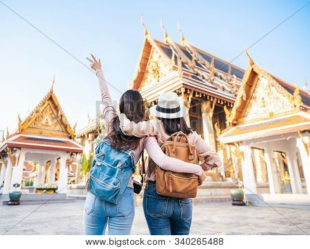 Rear View Of Two Asian Women Traveller Best Friends Having Fun During Vacation In Temple Of The Emer