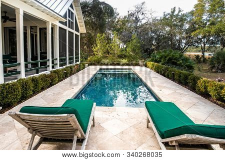 Beautiful back yard pool behind luxury home with garden.
