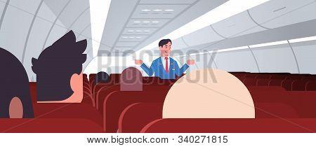 Steward Explaining Instructions For Passengers Male Flight Attendant In Uniform Showing Emergency Ex