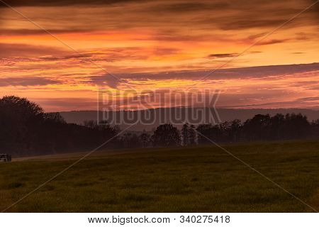 A Burning Red Sky With Silhouetted Forrest