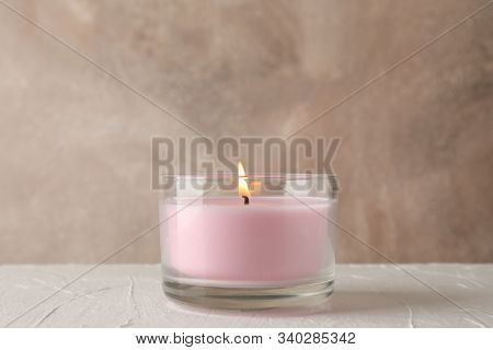 Pink Candle In Glass Jar On White Table Against Brown, Copy Space