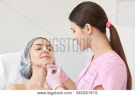 Doctor Cosmetologist With Ponytail Makes Rejuvenating Facial Injections Procedure For Tightening And