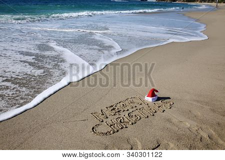 Christmas Words in sand on the beach. Santa's hat on a tropical beach. Merry Christmas written in sand with a Santa Claus Hat with ocean waves and blue sky in background. Merry Christmas.