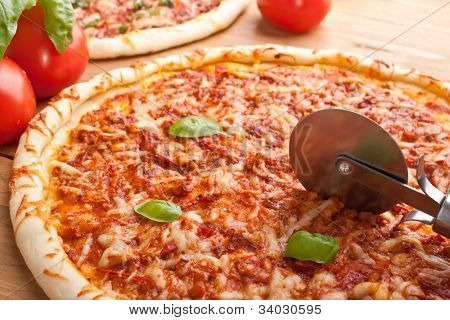 Margharita pizza with basil, tomato sauce and melted cheese on a wooden table