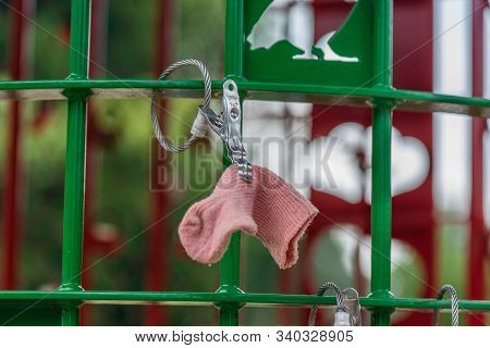 Pink Baby Sock Clipped To A Lost Item Rack In A Park