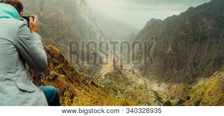 Rear View Of Traveler Making Photo Of Amazing Steep Mountainous Terrain With Lush Canyon Valley On T