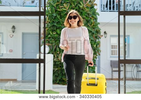Woman Guest Tourist With Suitcase In Hotel Lobby Interior. Beautiful Mature Woman Traveling, Modern