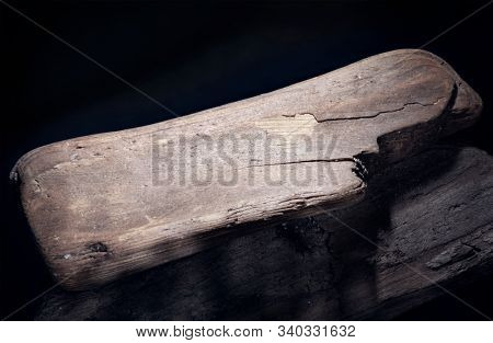 A piece of old wood thrown out by the water. Shelf for an exhibition. Rough wood surface. Natural pattern. Black background. Macro photo.