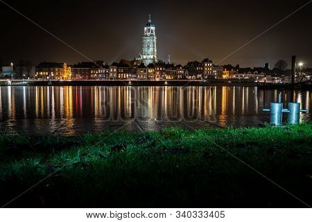 View Of  Medieval Dutch City With The Great Church Alongside The Ijssel River Wth Refelction In The