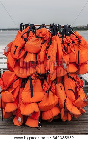 Many Orange Lifejackets Hanging On The Rack On Pier At The Sea