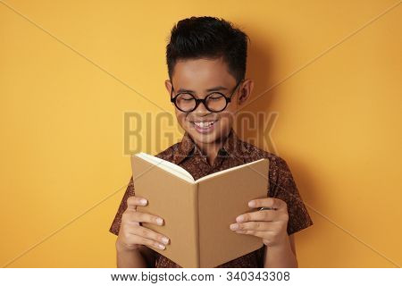 Portrait Of Smart Young Asian Student Boy Wearing Eyeglasses And Batik Shirt Smiling When Reading A