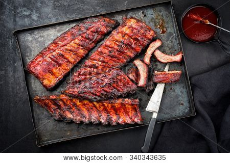 Barbecue pork spare ribs St Louis cut with hot honey chili marinade as top view on an old rustic metal board