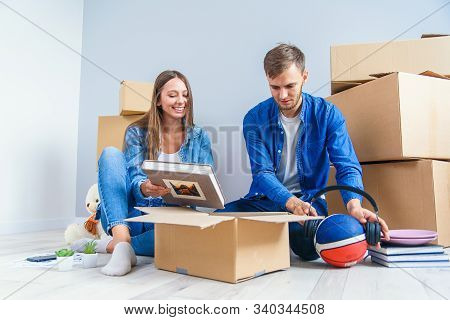 Young Couple Unpacking Things After Moving Into New House