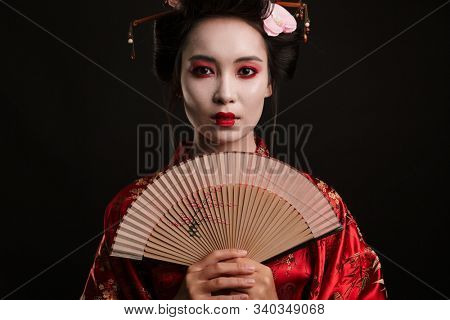Image of young geisha woman in traditional japanese kimono holding wooden hand fan isolated over black background