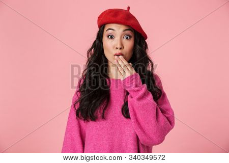 Image of surprised beautiful asian girl with long dark hair wearing beret expressing fright isolated over pink background