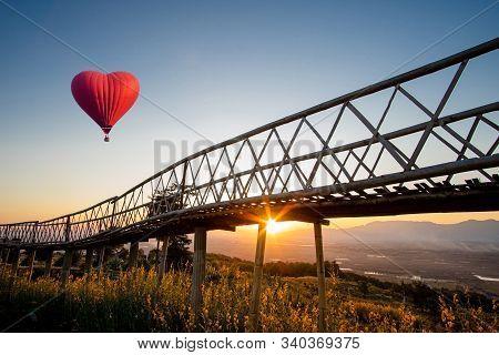 Red Hot Air Balloon In The Shape Of A Heart Over The  Sunset At Ban Doi Sa-ngo Chiangsaen, Chiang Ra