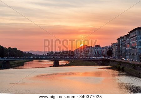 Fiery Sun Setting Along Arno River In Florence