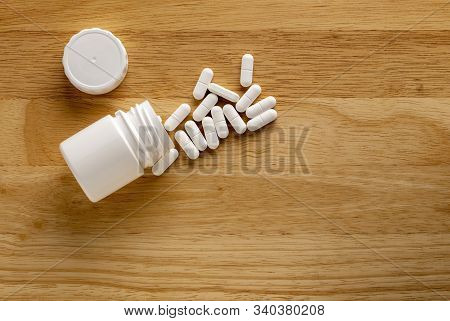 Medicinal Bottle And White Drugs On A Wooden Table