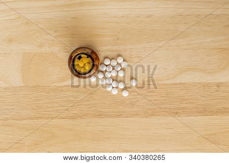 White Medicinal Antibiotics And Glass Bottle On A Wooden Background