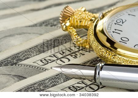 ink pen and watch on dollar money banknotes