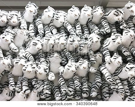 Group Of White Fluffy Tiger  Dolls Are Hanging On Wall In Toy Shop
