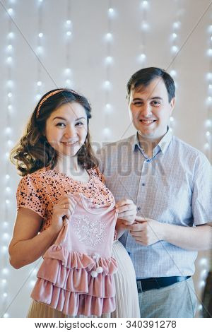 Loving Couple Embracing And Tockings Considers Childrens Clothes. Healthy Lifestyle Concept, Ivf Fas