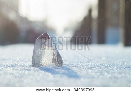 Snow-white Crystal Of Pure Transparent Quartz On Snow. Chalcedony Contrast On Background Of Blurred
