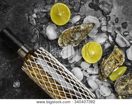 Oyster On Ice, Lemon Slices, Wine Bottle. Delicatessen And Gourment Food, Rich In Iodine, Antioxidan