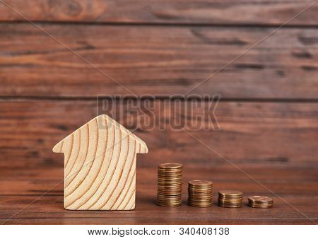 House Model And Coins On Wooden Background. Space For Text