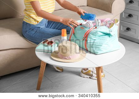 Woman Putting Items For Vacation In Bag Indoors, Closeup