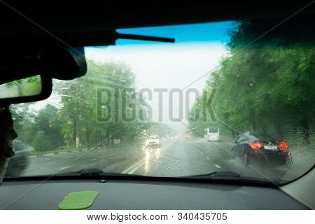 Driving Car In The Rain On Wet Road. Rainy Weather Through The Car Window. Rain Through Wind-screen