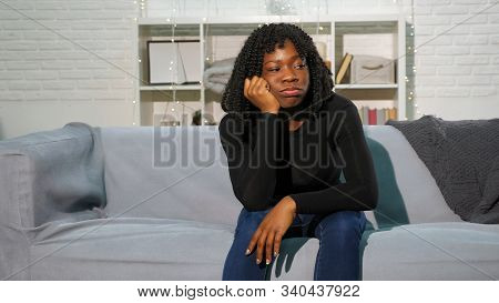 Bored Nice Black Girl With Fleecy Hair Sits On Grey Sofa Against White Wall With Bookshelves At Home