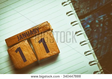 January 11th. Day 11 Of Month, Handmade Wood Cube With Date Month And Day Placed On A Lined Notebook