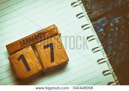 January 17th. Day 17 Of Month, Handmade Wood Cube With Date Month And Day Placed On A Lined Notebook