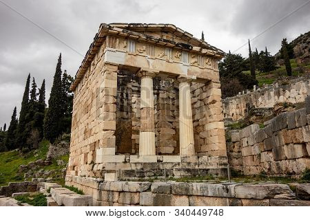 The Ancient Delphi City In Greece With Treasury Of Athenians In Cloudy Weather With Perspective View