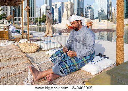 Abu Dhabi, Uae - December 14, 2019: Man Is Knitting Traditional Fishing Net