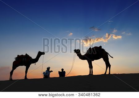 Silhouette Of Two Cameleers And Their Camels At Sand Dunes Of Thar Desert, Rajasthan, India. Sunset