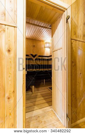 A Close-up Of  Entrance To Wooden Sauna, A Bath With A Large New Metal Stove And Benches With Beauti
