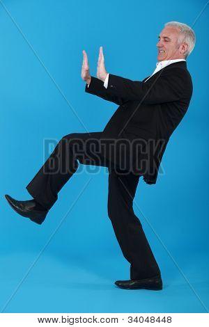 Elderly man pushing object poster