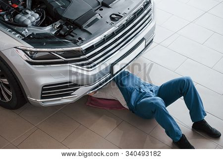 Lying Down On The Pink Colored Towel. Man In Blue Uniform Works With Broken Car. Making Repairings.