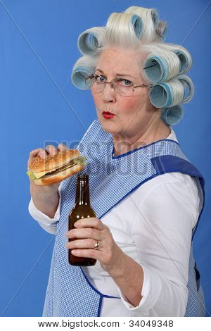 funny picture of grandma with hair curlers relishing cheeseburger with beer