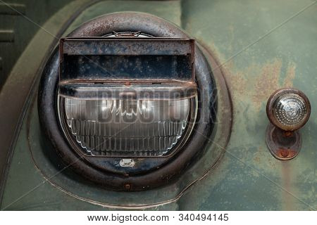 Headlight Of A Military Truck With Blackout Headlight Cover On It, Old-timer Vehicle From Wwii Perio