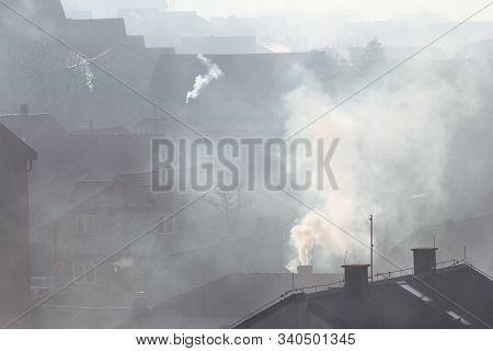 Smoking Chimneys At Roofs Of Houses Emits Smoke, Smog At Sunrise, Pollutants Enter Atmosphere. Envir