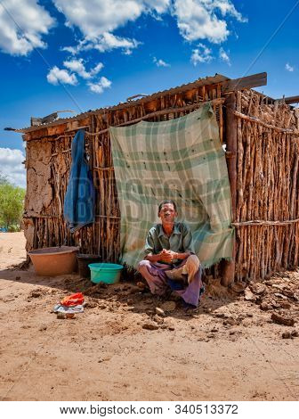 old bushman man in front of the shack from Central Kalahari, village New Xade in Botswana