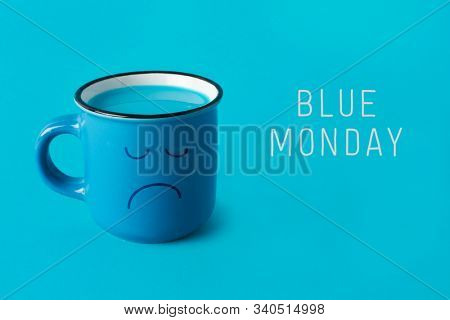 closeup of a blue mug, with a sad face drawn in it, and the text blue monday on a blue background
