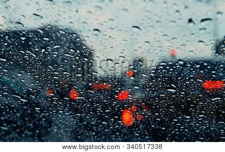 City Road Seen Through Rain Drops On The Car Windshield. Focus Is On Some Water Drops