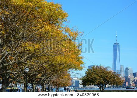 NEW YORK, NY - 04 NOV 2019: The World Trade Center seen from Ellis Island with fall foliage in the foreground.