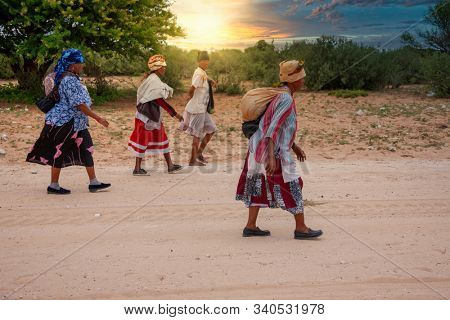 Group of four old bushman woman from Central Kalahari, village New Xade in Botswana, walking on a dirt road